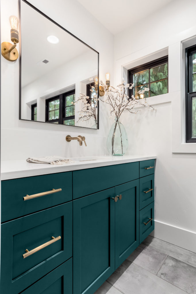 A bathroom with beautiful cabinets and finishes. The cabinet was painted in glossy deep teal color called Ocean Abyss. The hardware throughout  the cabinets is metallic gold or brassy colors.