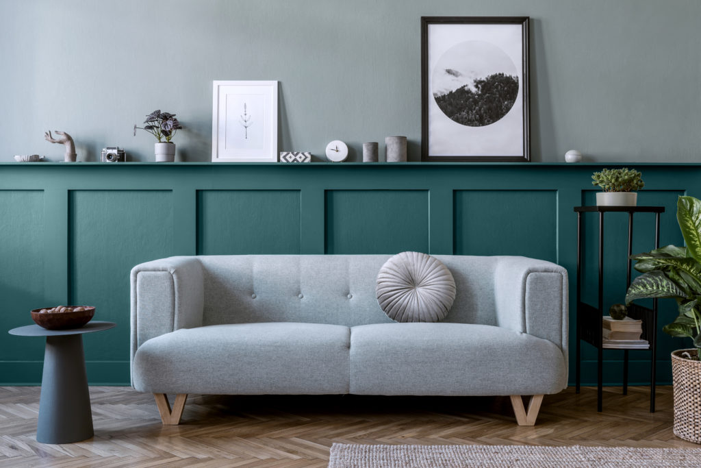 A living room featuring a lower accent wall.  The top of the wall is painted in an almost neutral blue-green color called Water.  The accent lower wall is called Ocean Abyss.  The room is decorated with neutral casual decorative elements raging from a light gray upholstered sofa, a black tall side table, and concrete gray color small decorative elements.