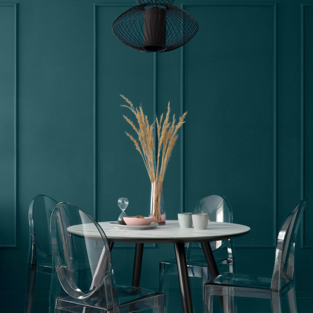 Fancy dining room with blue-green wall with molding and with modern table with black legs and marble style countertop, nice table decorations, four, new plastic chairs under black pendant lamp. The wall being featured is was painted in a deep teal color called Ocean Abyss.