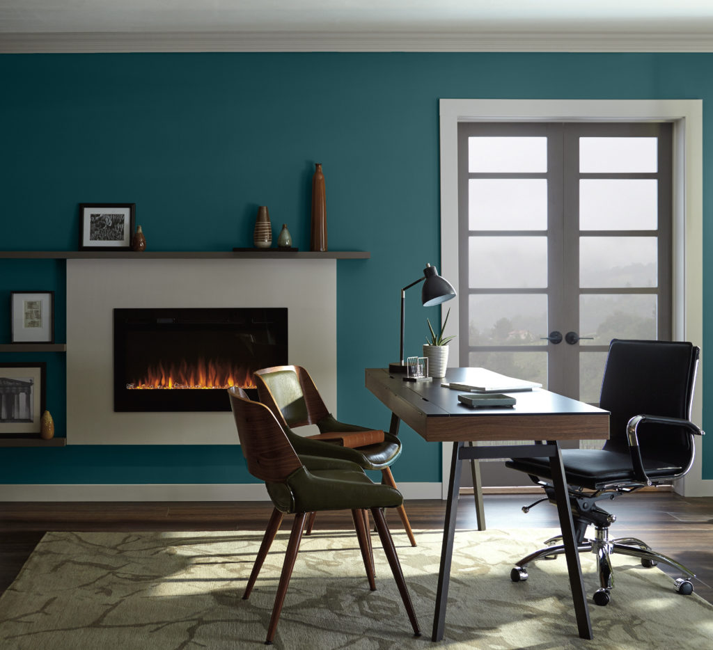 A contemporary office with a fireplace. the furniture used in the room has a retro feel too it.  There is also a double wood and glass door that allows you to see hazy green vista.