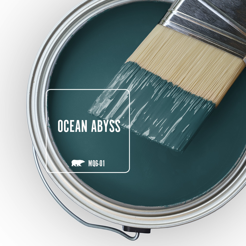 The top view of an open paint can, the color being featured is a dramatic teal color called Ocean Abyss.  There is a half dipped paint brush leaning on top of the open can.