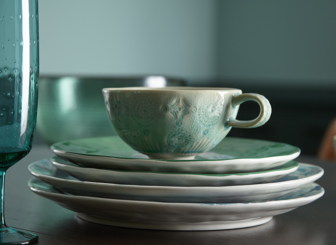A tight crop of blueish-green plates stacked with a tea cup on top of them ready for a calming evening.