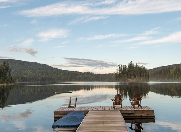 A wood dock that leads out to a quiet and calm lake.