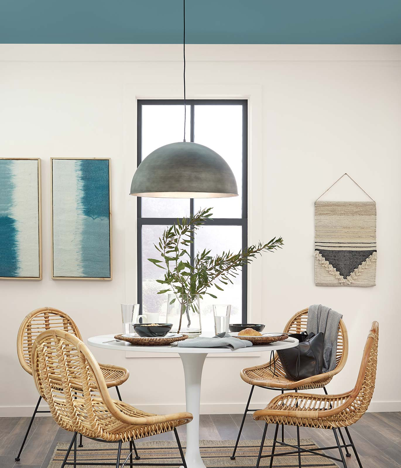 A casual dining area with a small round table and four rattan chairs surrounding it. Wall is painted in white with a blue painted ceiling. The atmosphere is relaxed and calm.