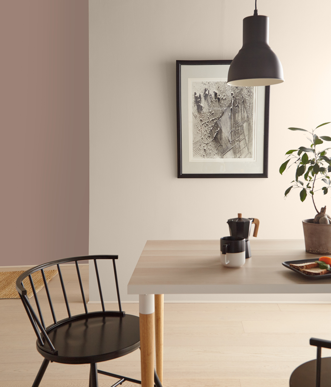A casual dining setting showing a corner of a table and chair. On the table is coffee, plate of food and potted plant. A light hangs down above the table.