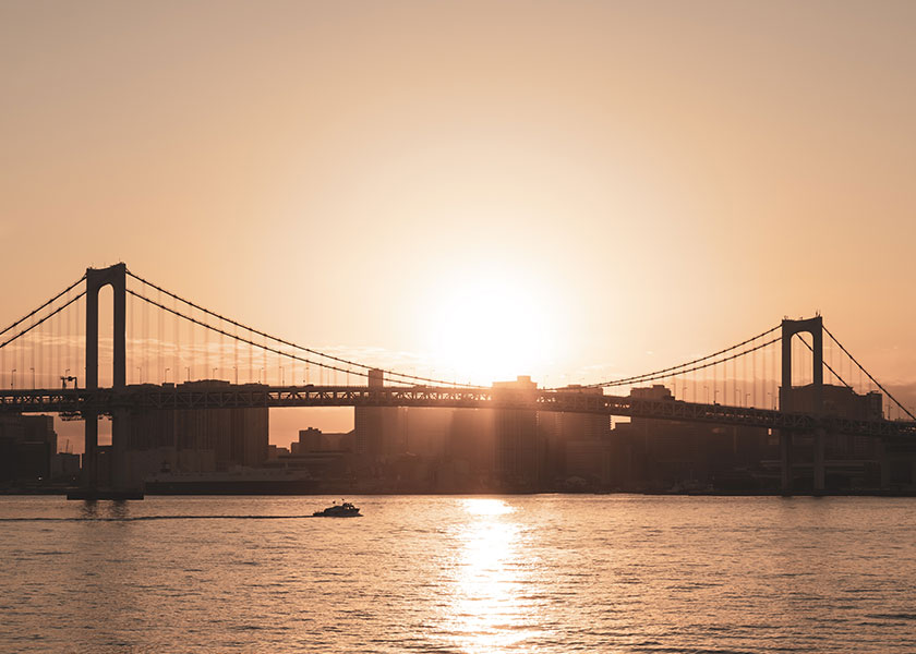 A pulled back view of a bridge that sits over a body of water. The sun is setting and glowing in the sky.