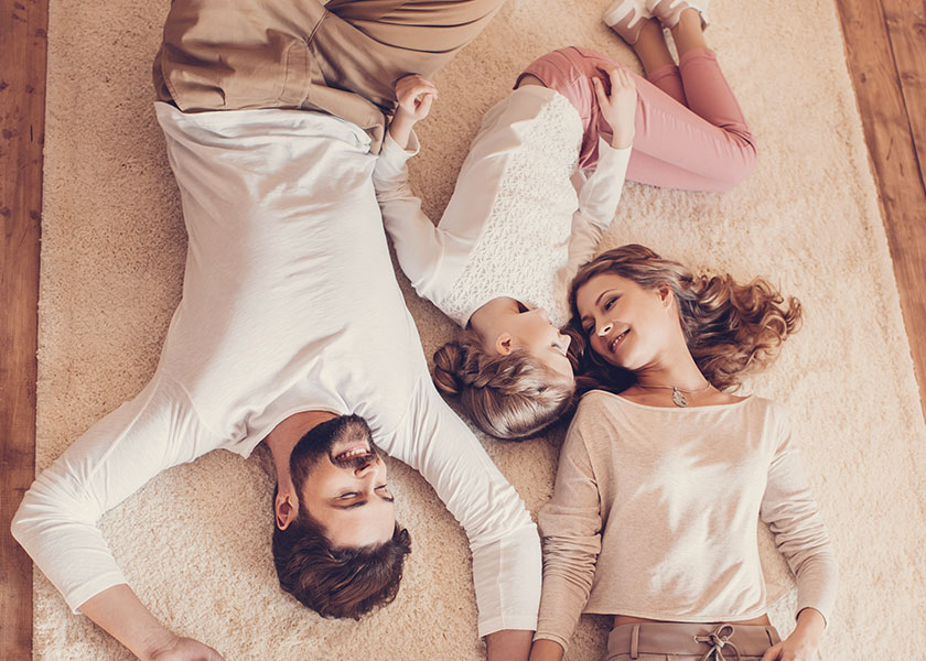 A family of three laying on the floor. The mother and daughter are looking into each other's face with a smile. The wife and husband are holding hands.