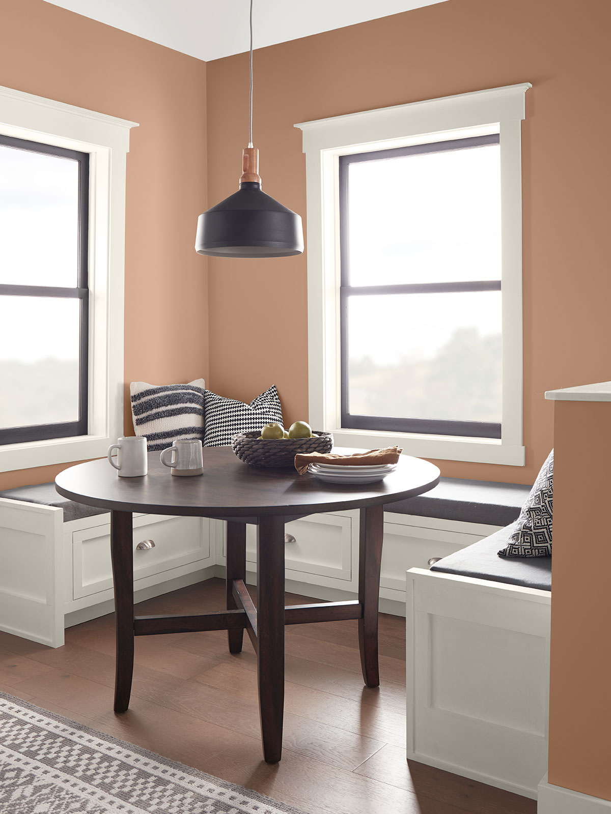 A kitchen nook with white built-in seats sitting below two windows. The table is a dark wood tone. The walls are painted in Canyon Dusk.