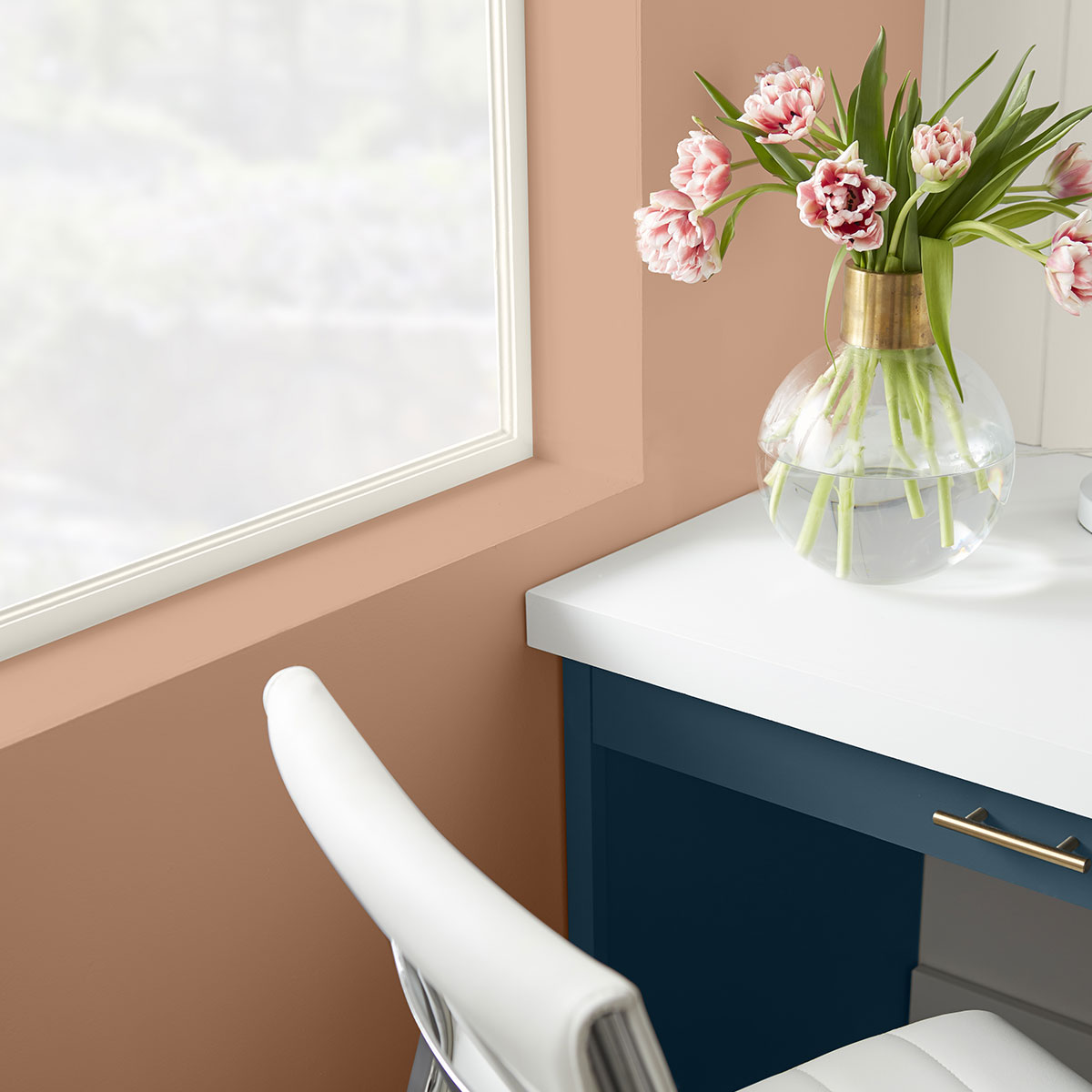 A corner of a desk with blue drawers and a white top. The wall that sits to the right is painted in Canyon Dusk.