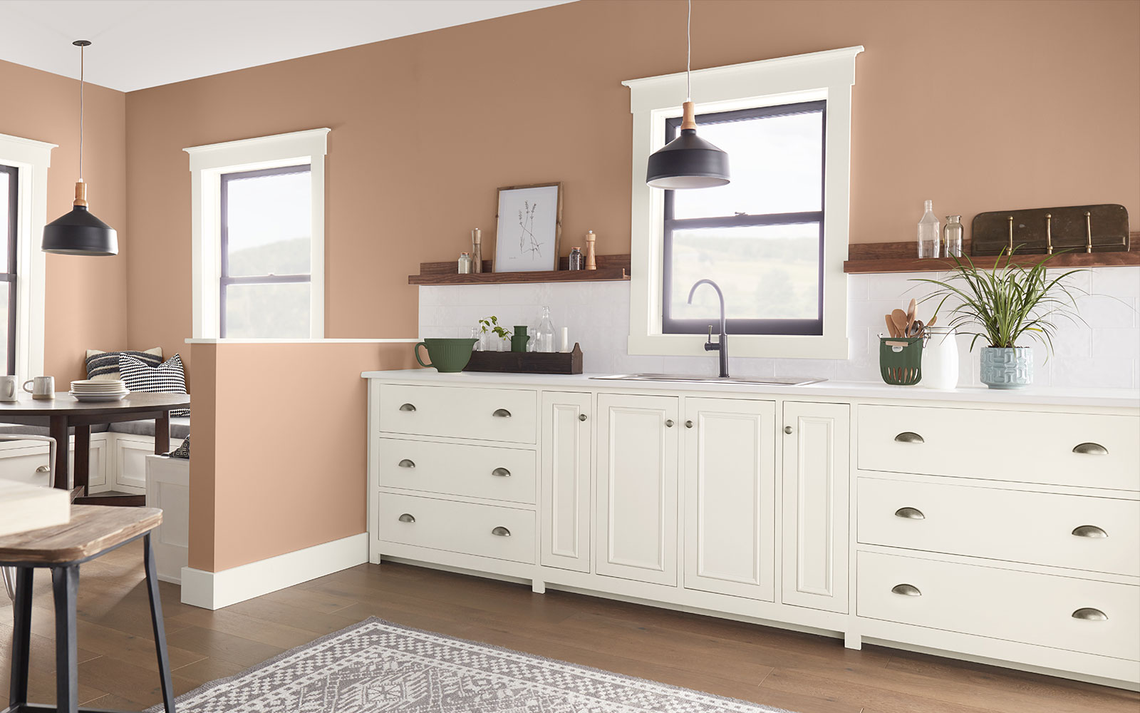 A kitchen image with three color swatches sitting beside it. The image displays the three colors: a dusty orange hue is used for the wall, a creamy white hue is used for the cabinets, and a dark green hue represents the plants sitting on the counters.
