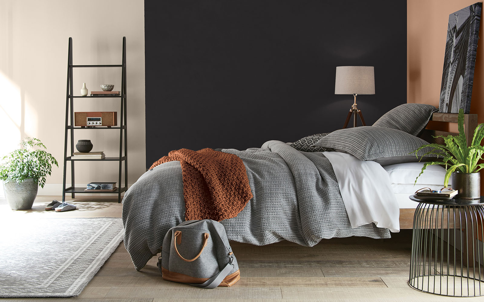A bed room image with four color swatches sitting beside it. The image displays the four colors: A black hue is used on the side wall of the bedroom, a creamy white hue is used for a wall just outside of the bed area, a terra-cotta orange is used for a blanket, and a dusty orange hue is used on the headboard wall.