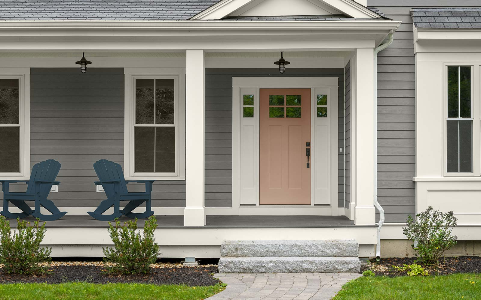 An exterior image with four color swatches sitting beside it. The image displays the four colors: a medium gray hue for the exterior body, a dark blue hue for the chair sitting on the porch, a dusty orange hue is used on the door, and a creamy white hue is used for the exteriors trim.