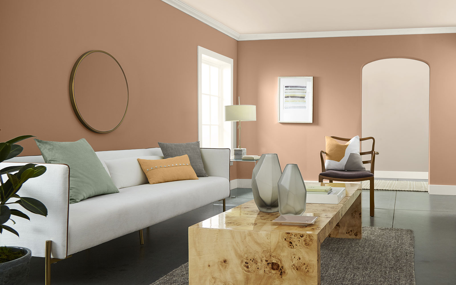 A living room image with four color swatches sitting beside it. The image displays the four colors: a light, but bright clean orange hue for a pillow  on the couch, a dusty orange hue is used on the wall, a creamy white hue is used for the trim, ceiling and couch, and a minty green is used for a pillow.