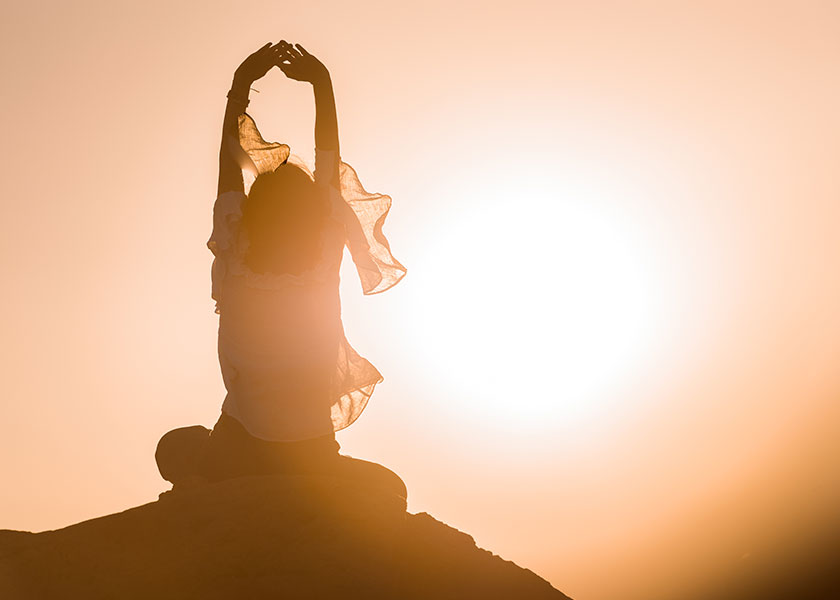 A woman sitting on the top of a mountain, meditating as the sun is setting behind her. The mood is tranquil.