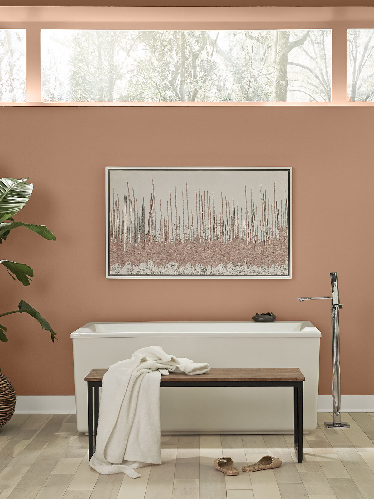 A bathroom showing a white tub and wood bench placed against a tall painted wall in the color Canyon Dusk.