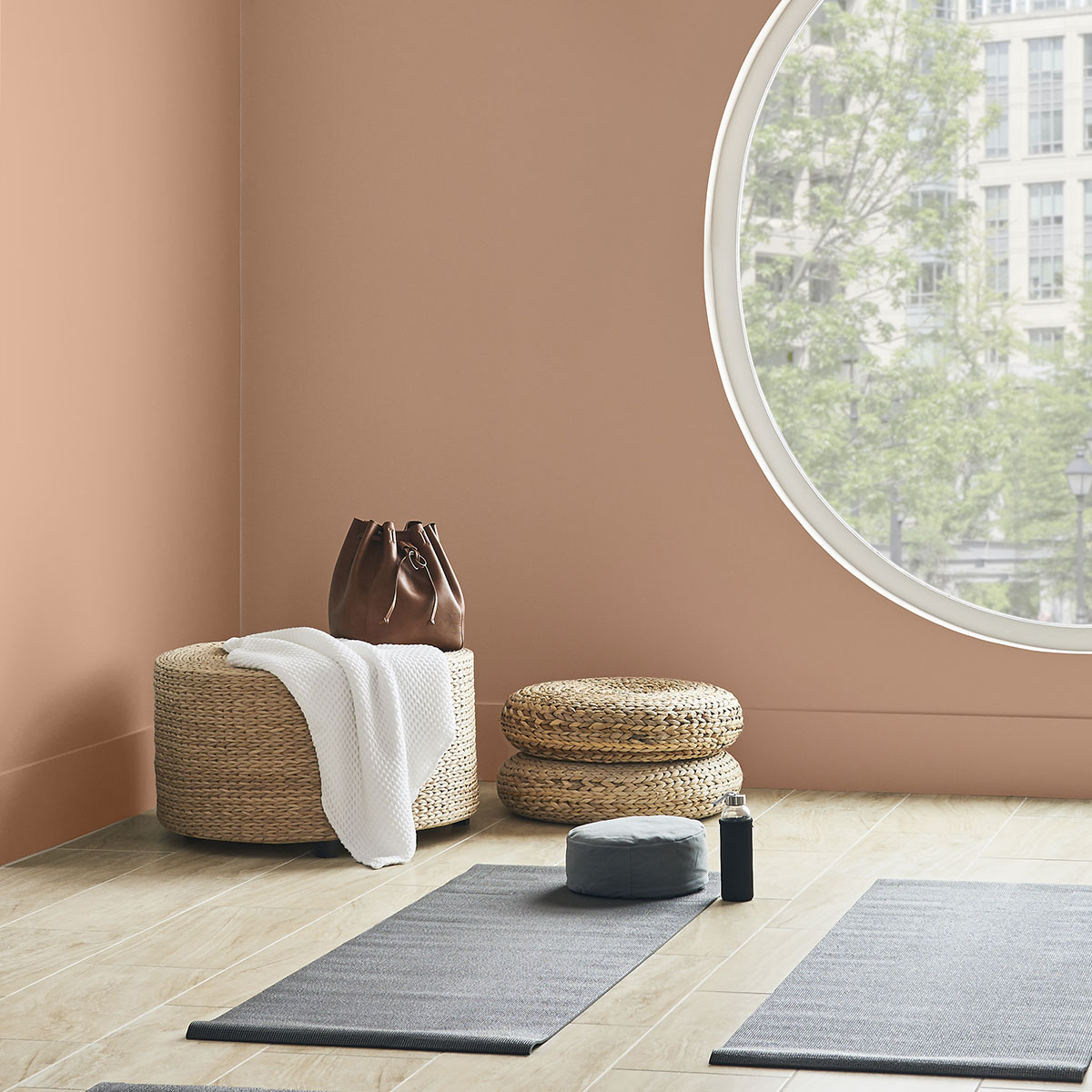 A cropped corner of a workout room with walls painted in Canyon Dusk. There is a large circle window on the wall bringing in a lot of light to the room. A rattan ottoman with a towel and purse placed on top sits in the corner. On the ground are yoga mats.