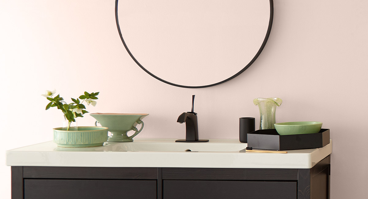 A bathroom sink with a dark cabinet, subtle green ceramic décor elements are placed atop.