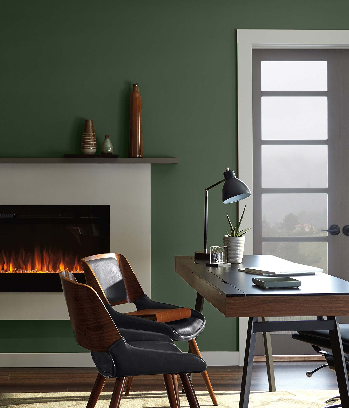 An office desk with a dark brown desk placed in front of a lit fireplace. Walls in the room are painted green. The mood is quiet and focused.