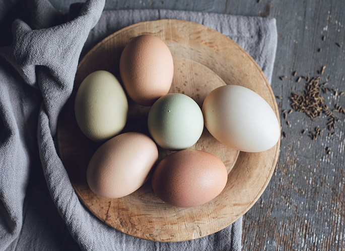 Ceramic eggs painted in subtle pastel colors sitting in a nest made of carved wood.