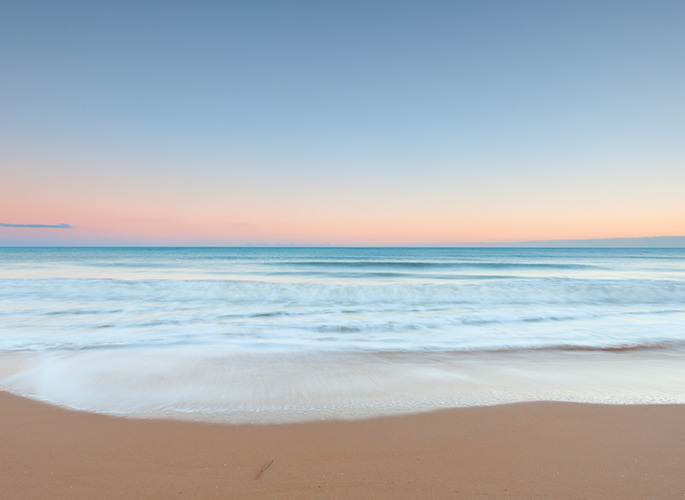 An ocean scene showing with the subtle colors of the sun rising painted in the background.