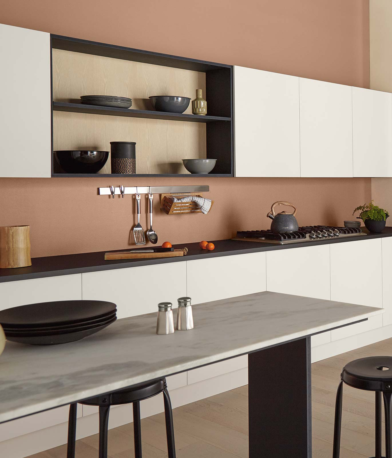 A kitchen painted in a burnt orange color with white cabinets and a white long table. The décor is subtle letting the color of the walls stand out.