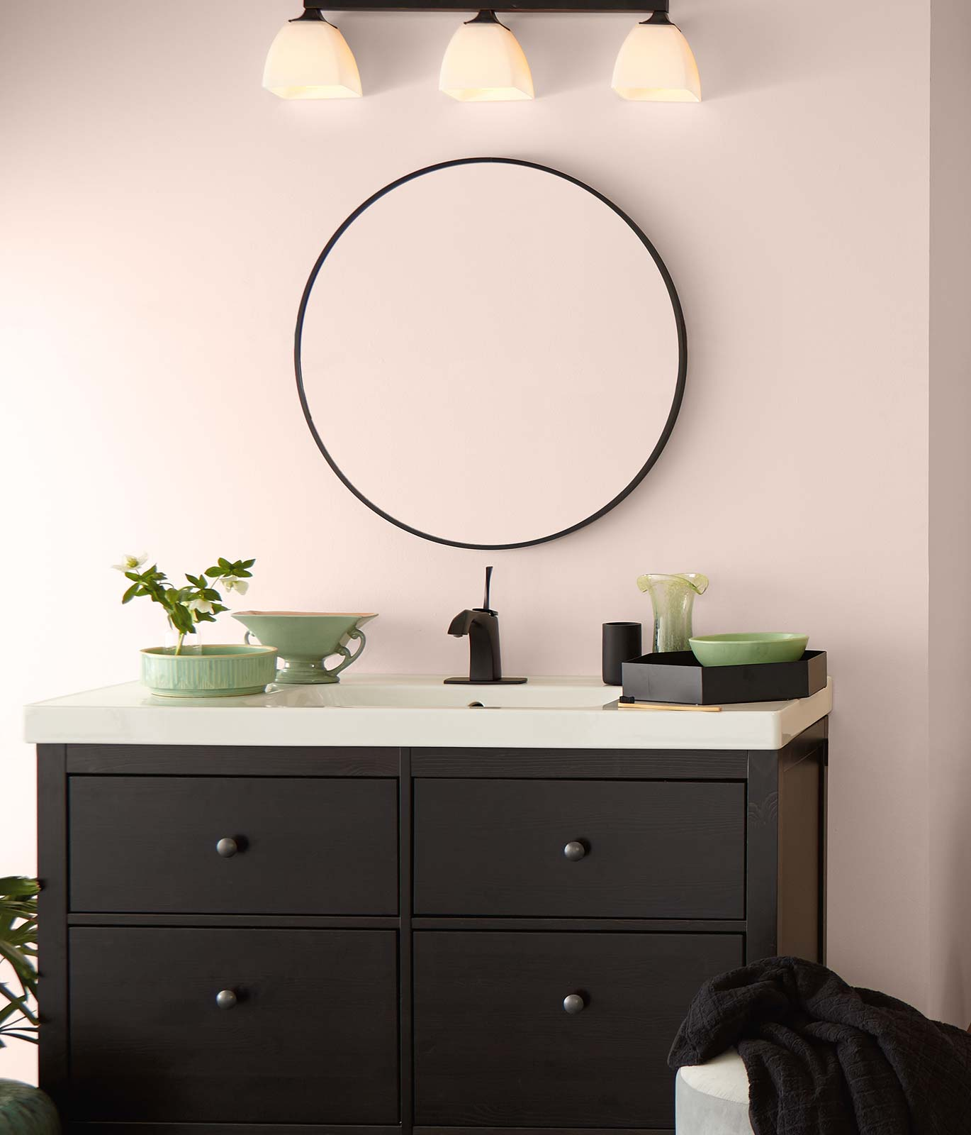 A bathroom with a white sink, brown cabinet and large round mirror. Walls are painted in a subtle pink color and room is decorated with green ceramic décor elements.