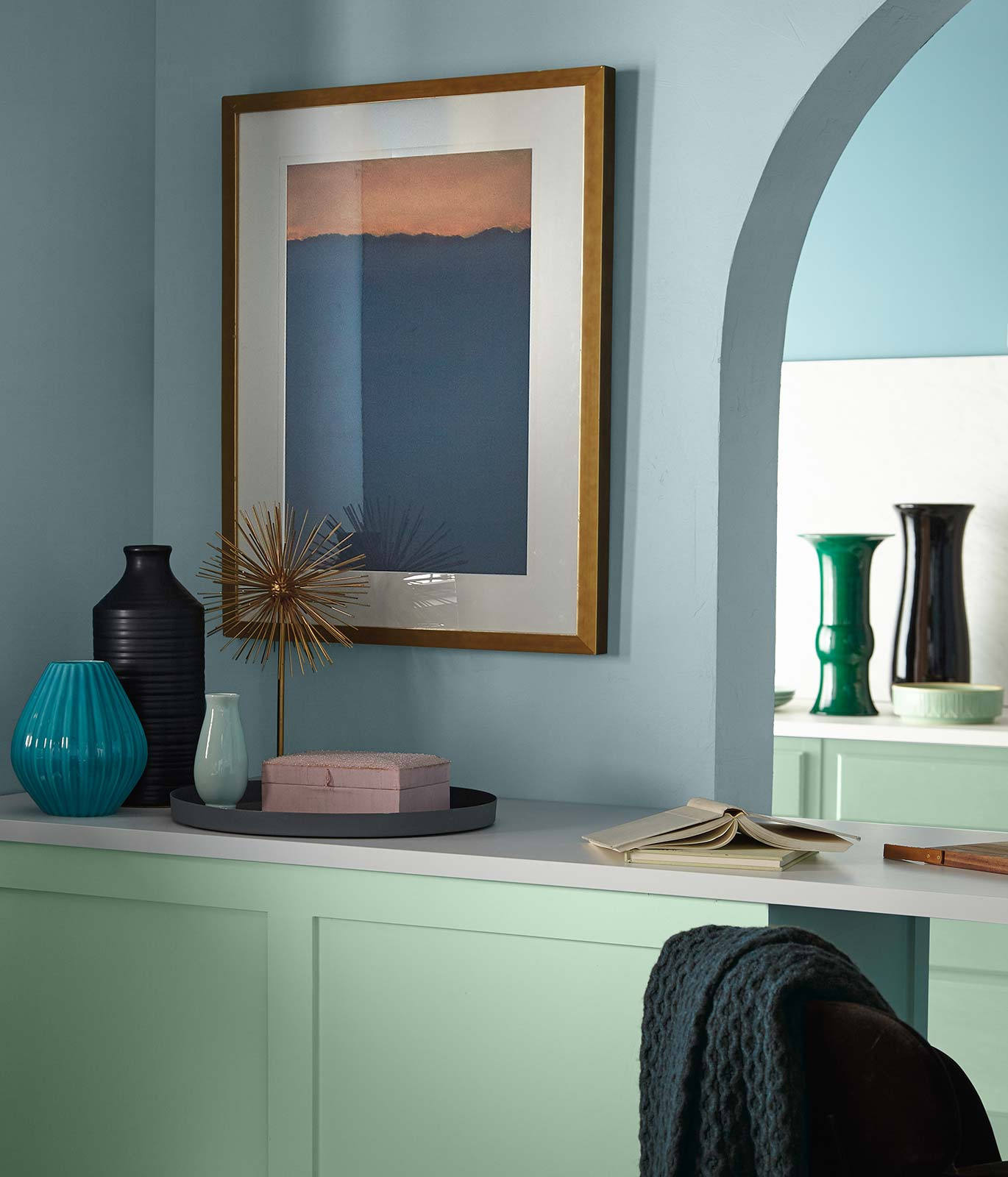 A buffet table painted in soft, subtle green with a white counter top sitting against a blue painted wall.