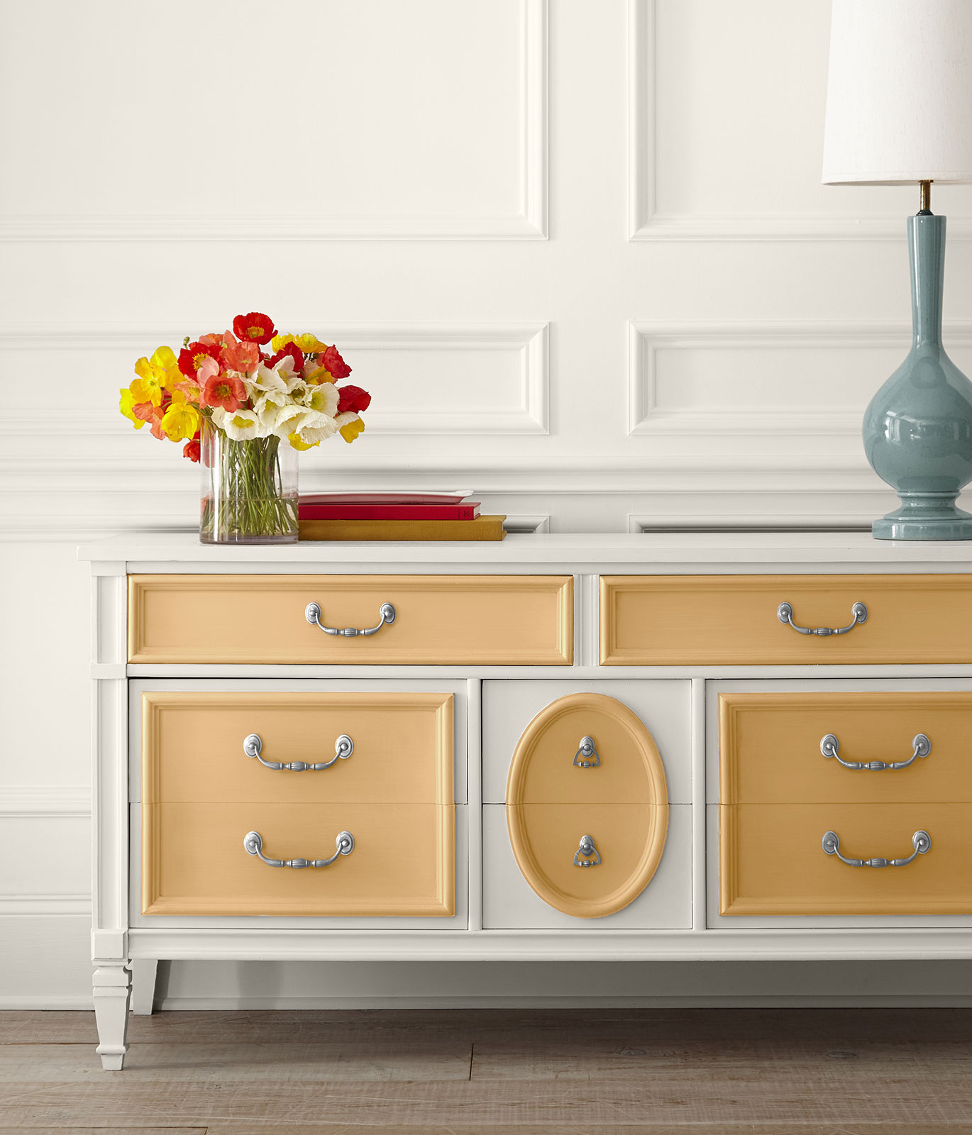 A dresser painted in white. To give a subtle pop of color, the drawer facings are painted in yellow-gold color.